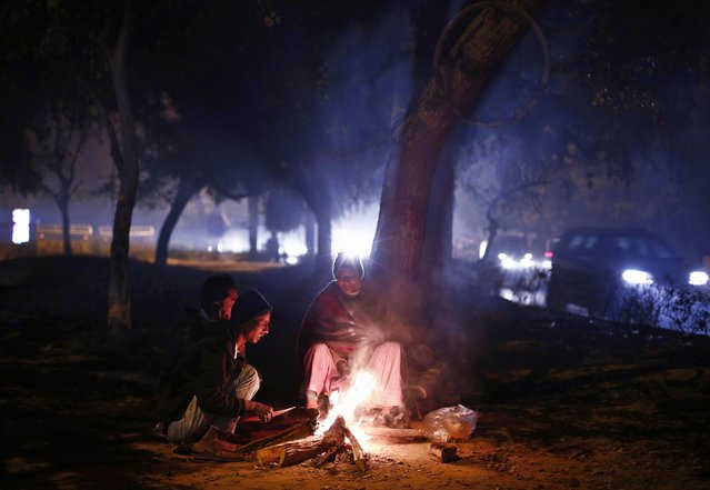 People warm themselves around a fire on road divider on a cold winter evening in New Delhi January 13, 2015. (Photo by Adnan Abidi/Reuters)