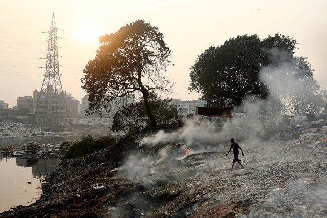 A man walks through the smoke that raises from burning wastes in Dhaka, Bangladesh, December 22, 2020. (Photo by Mohammad Ponir Hossain/Reuters)