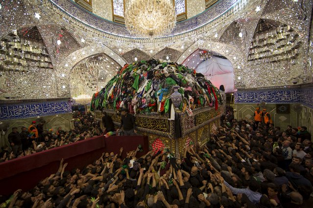 Shi'ite Muslim pilgrims reach out to touch the tomb of Imam al-Abbas located inside the Imam al-Abbas shrine to mark Arbaeen, in the holy city of Kerbala, southwest of Baghdad, December 3, 2015. (Photo by Ahmed al-Husseini/Reuters)