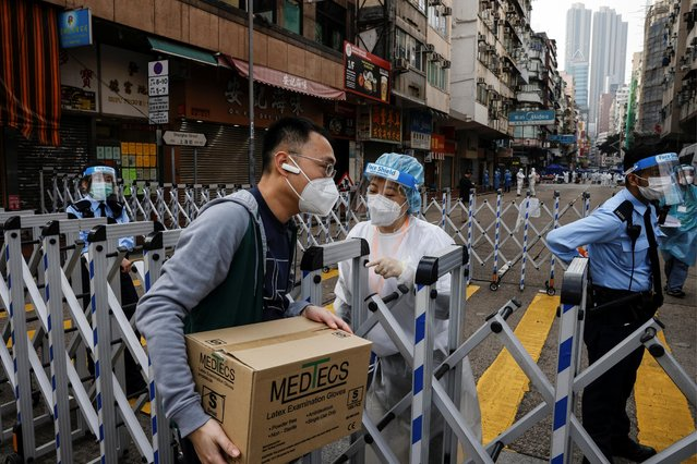 A health worker passes a package of gloves to a staff inside a locked down portion of the Jordan residential area to contain a new outbreak of the coronavirus disease (COVID-19), in Hong Kong, China on January 23, 2021. (Photo by Tyrone Siu/Reuters)