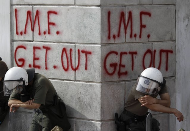 Greek riot policemen rest in front of graffiti written on the wall of a bank during violent demonstrations over austerity measures in Athens, in this May 5, 2010 file photo. (Photo by Yorgos Karahalis/Reuters)
