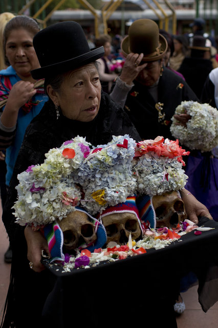 """A woman carries three decorated human skull or """"natitas"""", as she waits to be greeted by the priest inside the Cementerio General chapel, during the Natitas Festival celebrations, in La Paz, Bolivia, Tuesday, November 8, 2016. (Photo by Juan Karita/AP Photo)"""