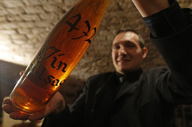 Thibaut Baldinger, manager of the wine cellar at the Strasbourg Hospital shows a bottle containing wine dating from 1472 at their cellar in Strasbourg, January 21, 2015. Known as the oldest wine in the world stored in a barrel, the wine will be transferred on Wednesday into a new barrel after the one it had been stored in since around 1715 showed leaks. (Photo by Vincent Kessler/Reuters)