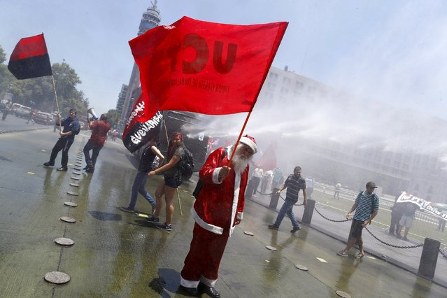 "A demonstrator dressed as Santa Claus holds up a flag as a riot police vehicle releases a jet of water during a protest against the private system of pension fund administrators in Santiago, Chile, December 10, 2015. The flag reads ""Classist Workers Union"". (Photo by Ivan Alvarado/Reuters)"