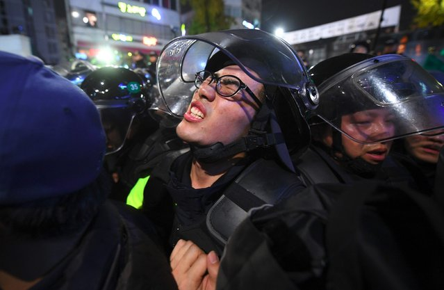 A riot policeman grimaces as he is squeezed between protestors and his colleagues as the protestors attempt to push through police barricades and march towards the presidential Blue House during an anti-government protest in central Seoul on November 12, 2016. Pressure on South Korea's scandal-hit president to resign escalated sharply on November 12, with organisers claiming a million-strong turnout at one of the largest – and loudest – anti-government protests the country has ever witnessed. (Photo by Jung Yeon-Je/AFP Photo)