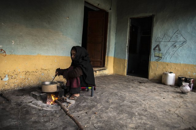 A girl cooks over a wood-burning fire at her house on Margalla Hills in Islamabad January 22, 2015. (Photo by Zohra Bensemra/Reuters)