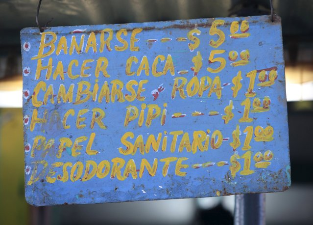 A signboard lists out the charges to use a mobile ecological bathroom in Vertientes, Camaguey province November 13, 2015. (Photo by Enrique de la Osa/Reuters)