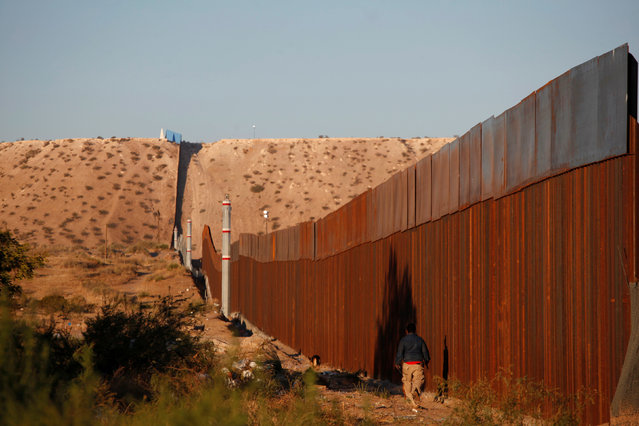 A man walks next to a section of the wall separating Mexico and the United States, on the outskirts of Ciudad Juarez, Mexico, November 12, 2016. (Photo by Jose Luis Gonzalez/Reuters)