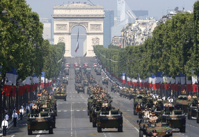 French soldiers stand in an armored vehicle during the Bastille Day parade in Paris, Sunday, July 14, 2013. Troops from 13 African countries who backed France in a war against al-Qaida-linked extremists in Mali marched with the French military during the Bastille Day parade in Paris on Sunday to honor their role in the conflict.  The Arc de Triomphe is seen in background. (Photo by Francois Mori/AP Photo)