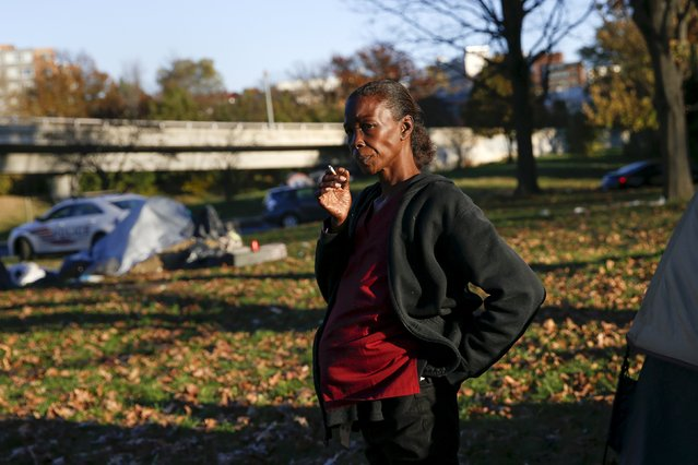 "Lovenia Evans, who is pregnant, smokes a cigarette by her tent between the Watergate and Whitehurst Freeway in Washington D.C., November 16, 2015. ""This is my second week in this tent, it's better to be here than laying on the street or sidewalk. I'm pregnant and they would like to me to come off the street"", Evans said. (Photo by Shannon Stapleton/Reuters)"