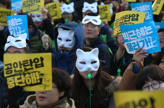 South Korean protesters wear masks and hold placards as they gather for a rally against President Park Gyun-Hye and the government's policies, in Seoul, South Korea, December 19, 2015. Park Gyun-Hye stated on November 16 that local protesters in masks could be infiltrated by members of Islamic State (IS). The protesters gathered to demand improvement of the government's labor policy and the resignation of South Korean president Park. (Photo by Yang Ji-Woong/EPA)