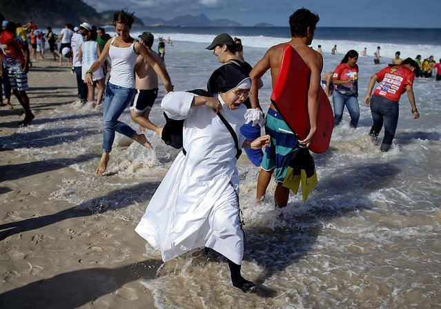 A nun reacts as the tide comes in on Copacabana beach. (Photo by Victor R. Caivano/Associated Press)