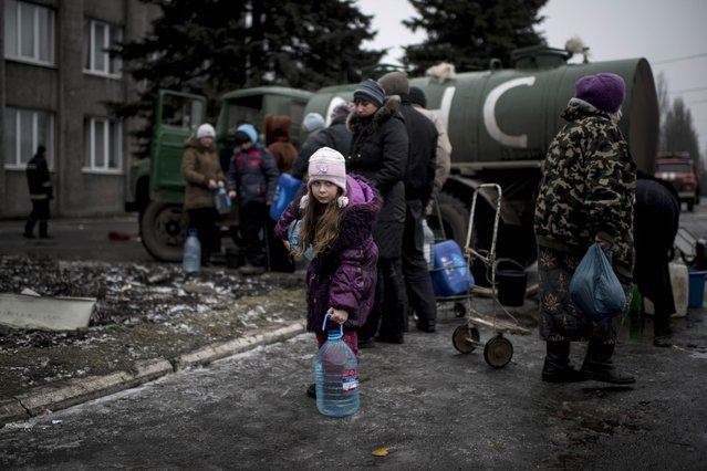 A girl holds a water bottle in the town of Debaltseve, eastern Ukraine, Friday, February 6, 2015. Pro-Russia rebels and the Ukrainian authorities agreed Friday on a humanitarian corridor to evacuate civilians from the epicenter of fighting in eastern Ukraine as German and French leaders prepared to bring their peace plan to Moscow. (Photo by Evgeniy Maloletka/AP Photo)