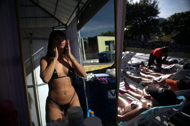 """A woman wearing a masking tape bikini, is reflected in a mirror as she puts sunblock on her face before sunbathing on a terrace to have the perfect bikini line (""""marquinha"""" in Portuguese), at the Erika Bronze spa in Rio de Janeiro, Brazil, November 17, 2016. (Photo by Pilar Olivares/Reuters)"""