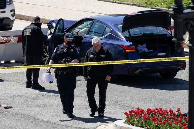 """U.S. Capitol Police officers near a car that crashed into a barrier on Capitol Hill in Washington, Friday, April 2, 2021. The suspect who was shot dead by cops in the fatal car-and-knife rampage at the US Capitol on Friday was a devoted follower of """"Nation of Islam"""" leader Louis Farrakhan, according to his social media. Noah Green, 25, was named by multiple media outlets as the suspected driver who ploughed a blue Nissan Altima sedan into a barrier outside the Capitol in D.C on Friday afternoon – killing cop William """"Billy"""" Evans and injuring another officer. (Photo by J. Scott Applewhite/AP Photo)"""