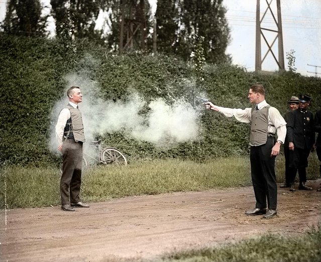W. H. Murphy and his associate demonstrating their bulletproof vest on October 13, 1923. Colorized by zuzahin on Reddit. (Photo by National Photo Company)