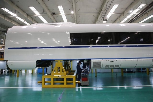 An employee works on a final assembly line for CRH380B, a high speed train model, at China CNR's Tangshan Railway Vehicle's factory in Tangshan, Hebei province, February 11, 2015. (Photo by Kim Kyung-Hoon/Reuters)