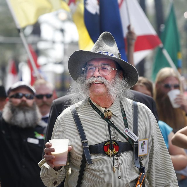 Stewart Eastman of Abita Springs, Louisiana enjoys a beer while parading through the French Quarter to kick off the fourth annual Just For Men National Beard and Moustache Championships Saturday, September 7, 2013 in New Orleans. Contestants competed in 18 different categories including Dali, full beard natural and sideburns. (Photo by Susan Poag/AP Photo)