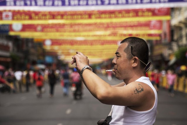 A Chinese tourist with a tattoo of China's late Chairman Mao Zedong takes pictures in Bangkok's Chinatown decorated for the Chinese Lunar New Year February 19, 2015. (Photo by Damir Sagolj/Reuters)