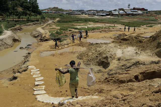 In this June 28, 2018, photo, Rohingya refugees carry construction material to an extended area of Kutupalong refugee camp in Bangladesh where some refugees living in areas considered at risk of landslides and flooding were relocated to. The monsoon season has arrived in Bangladesh, bringing fresh dangers to the 900,000 Rohingya refugees who live in ramshackle huts on unstable hills. (Photo by Wong Maye-E/AP Photo)