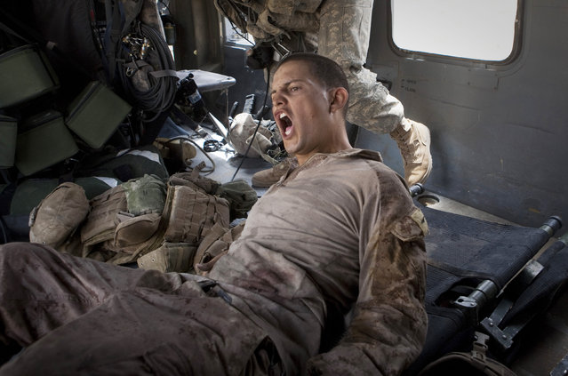 """Lance Cpl. Blas Trevino of the 1st Battalion, 5th Marines, shouts out as he is rescued on a medevac helicopter from the U.S. Army's Task Force Lift """"Dust Off"""", Charlie Company 1-214 Aviation Regiment after he got shot in the stomach outside Sangin, in the Helmand Province of southern Afghanistan on June 11, 2011. The Army's 'Dust Off' crew needed two attempts to get him out, as they were fired upon and took five rounds of bullets into the tail of their aircraft. (Photo by Anja Niedringhaus/AP Photo/File)"""