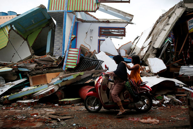 A woman and child ride a motorcycle past damaged buildings following this week's strong earthquake in Meureudu market, Pidie Jaya, Aceh province, Indonesia December 9, 2016. (Photo by Darren Whiteside/Reuters)