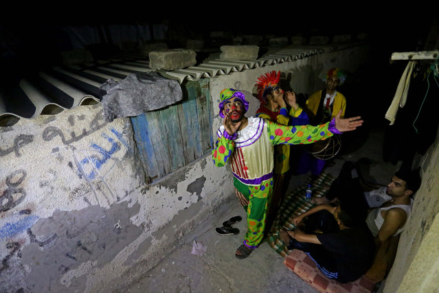 Three Palestinian men wearing clown costumes, walk the Gaza City streets with their drums to wake people for pre-dawn meal of sahur, the last meal before a long day of fasting that starts with the call to prayer at sunrise, in Gaza on May 23, 2018. (Photo by Ashraf Amra/Anadolu Agency/Getty Images)