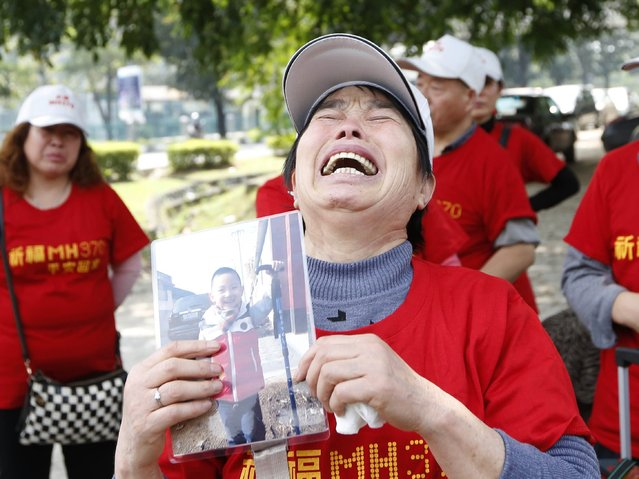 Wang Run Xiang, 58, the mother of a passenger aboard missing Malaysia Airlines Flight MH370, holds a picture of her grandson whose father was aboard the plane as she talks with the media outside the Malaysia Airlines headquarters in Kuala Lumpur February 12, 2015. Families of passengers aboard missing Malaysia Airlines Flight MH370 arrived from China to demand answers from the Malaysian government about the whereabouts of the aircraft. Malaysia declared last month the disappearance of Malaysia Airlines Flight MH370 an accident, clearing the way for the airline to pay compensation to victims' relatives while the search for the plane goes on. The Boeing 777 aircraft disappeared on March 8 last year, carrying 239 passengers and crew shortly after taking off from the Malaysian capital of Kuala Lumpur, bound for Beijing.   REUTERS/Olivia Harris