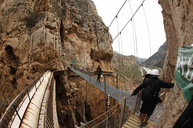 Journalists take pictures as they walk along the new Caminito del Rey (The King's Little Pathway) in El Chorro-Alora, near Malaga, southern Spain March 15, 2015. (Photo by Jon Nazca/Reuters)