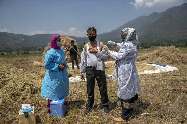 A health worker administers the AstraZeneca vaccine for COVID-19 in a paddy field in Tral village south of Srinagar, Indian controlled Kashmir, Saturday, June 5, 2021. (Photo by Dar Yasin/AP Photo)