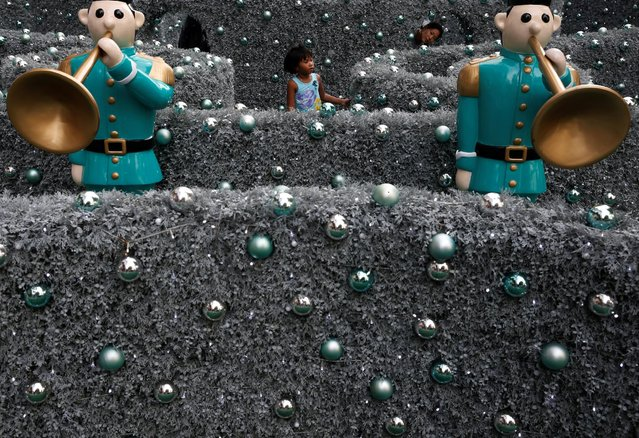 A child plays in a maze among Christmas decorations outside a mall in Singapore December 19, 2016. (Photo by Edgar Su/Reuters)