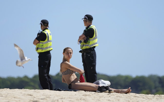 A woman sunbathes, while police patrol nearby, as a meeting of G7 leaders takes place in St. Ives, Cornwall, England, Saturday, June 12, 2021. Leaders of the G7 gather for a second day of meetings on Saturday, in which they will discuss COVID-19, climate, foreign policy and the economy. (Photo by Jon Super/AP Photo)
