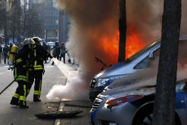 "Fireworkers extinguish police vehicles set of fire by anti-capitalist ""Blockupy"" protesters near the European Central Bank (ECB) building before the official opening of its new headquarters in Frankfurt March 18, 2015. (Photo by Michael Dalder/Reuters)"