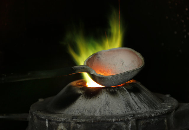 The mixture of copper and tin is melting in the Blondeau foundry during the preparation of the Rio 2016 bronze bells in La Chaux-de-Fonds, Switzerland January 21, 2016. (Photo by Denis Balibouse/Reuters)