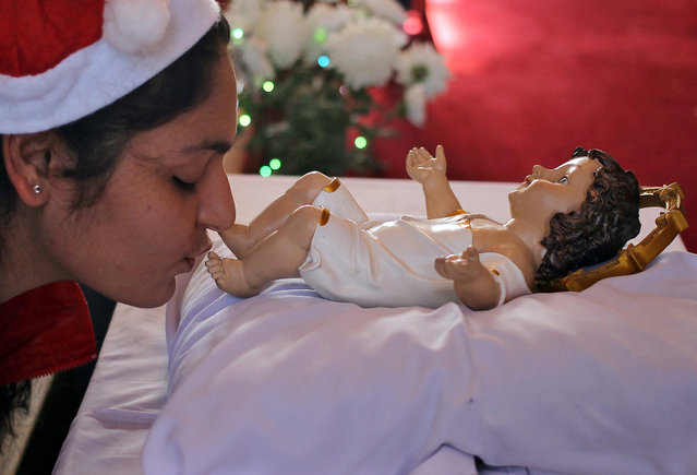 A woman kisses a figure of the baby Jesus at a church during Christmas celebrations in Jammu December 25, 2016. (Photo by Mukesh Gupta/Reuters)