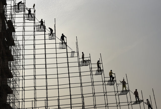 Indian laborers standing on scaffolding shift steel rods from the ground to the top of an under construction hospital building in Greater Noida, near New Delhi, India, Thursday, November 22, 2018. Building work in the capital region has resumed after authorities last week lifted a ban on construction activities they had imposed to combat air pollution. (Photo by R.S. Iyer/AP Photo)