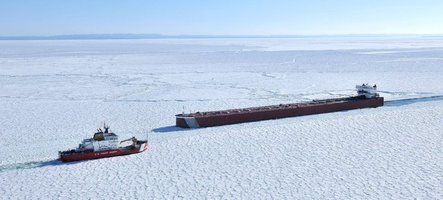 The U. S. Coast Guard cutter Mackinaw, left, works in thick ice to break out the freighter Edwin Gott in Whitefish Bay of Lake Superior, Friday, March 27, 2015. The shipping season began three days earlier, but heavy ice in the eastern end of the lake has a fleet of icebreakers working to open shipping channels for shipping. (Photo by John L. Russell/AP Photo)