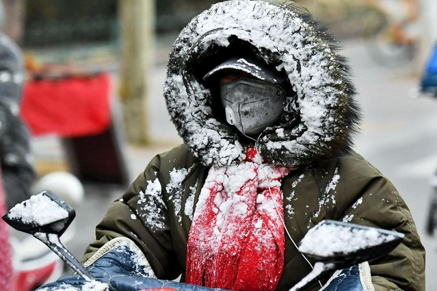 A citizen covered with snow on clothes drives a vehicle on a road on December 5, 2018 in Shijiazhuang, Hebei Province of China. National Meteorological Center of CMA on Wednesday issued a blue alert for a cold wave. (Photo by Zhai Yujia/China News Service/VCG via Getty Images)