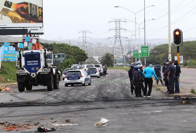 Police, on right, patrol a street in Durban, South Africa, Friday July 9, 2021, after protesters erected burning barricades to protest the imprisonment of former president Jacob Zuma. The Pietermaritzburg High Courtcourt has rejected Zuma's request to postpone his jail term of 15-months for contempt. (Photo by AP Photo/Stringer)