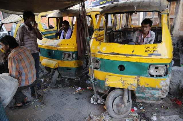Daily wage laborers sit inside scrap autorickshaws and drink tea in Allahabad, India, Friday, March 20, 2015. The laborers earn about US$ 5 a day. (Photo by Rajesh Kumar Singh/AP Photo)