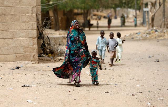A woman walks with her child in Dapchi, Yobe state, Yobe state, Nigeria February 27, 2018. (Photo by Afolabi Sotunde/Reuters)