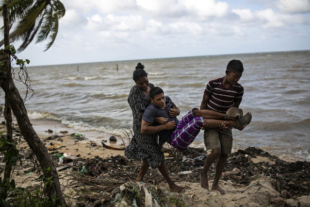 """In this Jan. 30, 2018 photo, Miskito diver Charles """"Charly"""" Melendez, 28, is carried by his 10-year-old son Jason and wife Kenia from their rented room along the shore in Puerto Lempira, Honduras, to a smoother ground for his wheelchair. Melendez said he been diving since he was 16 and had harvested 60 pounds of lobster on the day he was left paralyzed by decompression sickness. (Photo by Rodrigo Abd/AP Photo)"""