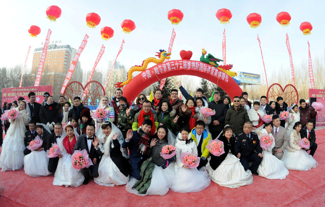 Couples pose for pictures during a mass wedding on the second day of Harbin's International Ice Festival, in Harbin, Heilongjiang province, China, January 6, 2017. (Photo by Reuters/Stringer)
