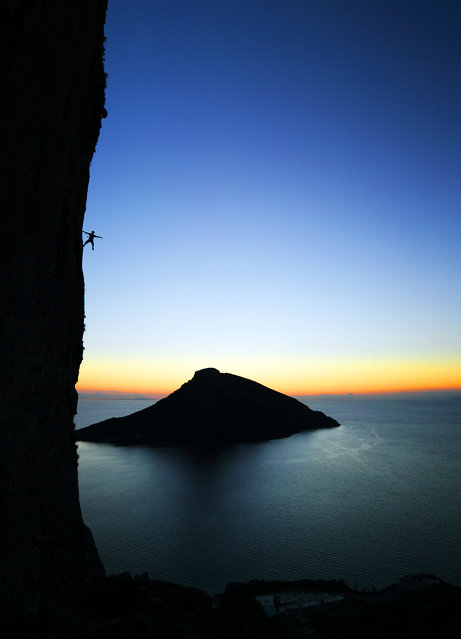 A climber poses on a rock during a climb in Kalymnos, Greece. (Photo by Adam Kokot/Caters News Agency)