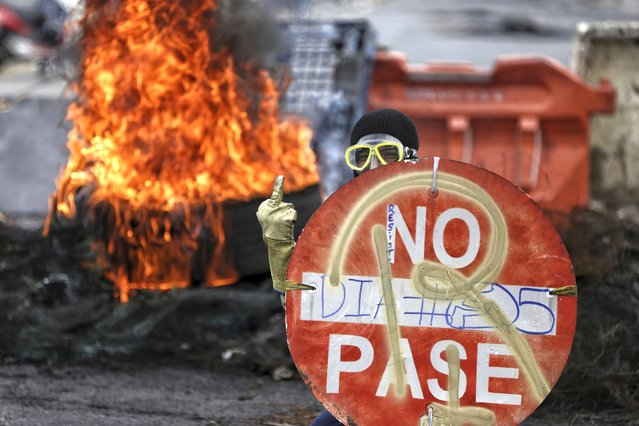 A protester protects himself with a traffic sign as he gestures obscenely at police during a national strike against tax reform in Cali, Colombia, Monday, May 3, 2021. Colombia's President Ivan Duque withdrew the government-proposed tax reform on Sunday. (Photo by Andres Gonzalez/AP Photo)