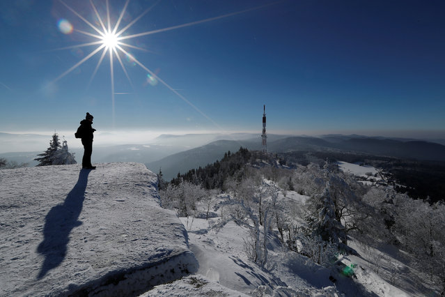 A hiker with snow-shoes stands on a rock on the summit of the Donon mountain as he enjoys a cold and sunny winter day in the Vosges mountains, in Granfontaine, near Strasbourg, France, January 19, 2017. (Photo by Christian Hartmann/Reuters)