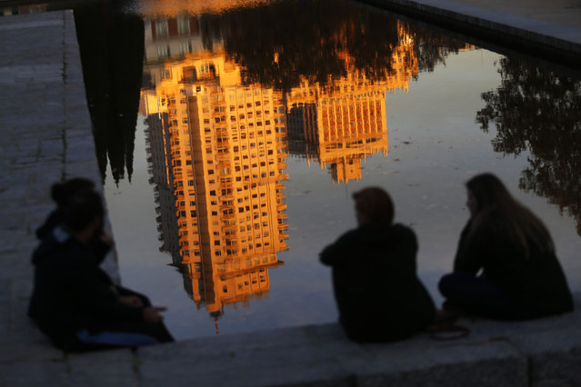 People sit next to a pool where the Tower of Madrid skyscraper is reflected at sunset in Madrid, Thursday, November 26, 2015. The tower was the tallest in Spain since it was finished in 1957 until 1982. (Photo by Francisco Seco/AP Photo)