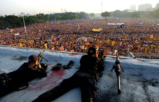 Members of a police SWAT team scan the horizon as they watch a sea of devotees surge towards the statue of the Black Nazarene during the annual religious procession in Manila on January 9, 2014. Hundreds of thousands of barefoot devotees poured into the capital for one of the world's biggest Catholic parades honouring an ebony statue of Jesus Christ they believe has miraculous powers. (Photo by Ted Aljibe/AFP Photo)