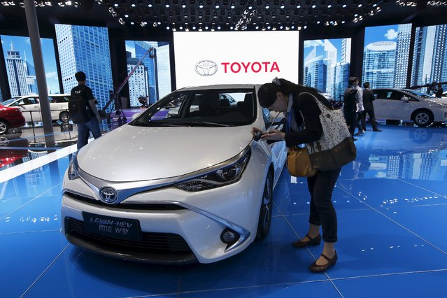 A woman takes pictures of a Toyota Levin HEV car during the 16th Shanghai International Automobile Industry Exhibition in Shanghai, April 20, 2015. Foreign automakers continue to plough money into factories in China, the world's largest car market, even as the biggest economic slowdown in a quarter of a century crimps sales growth. (Photo by Aly Song/Reuters)