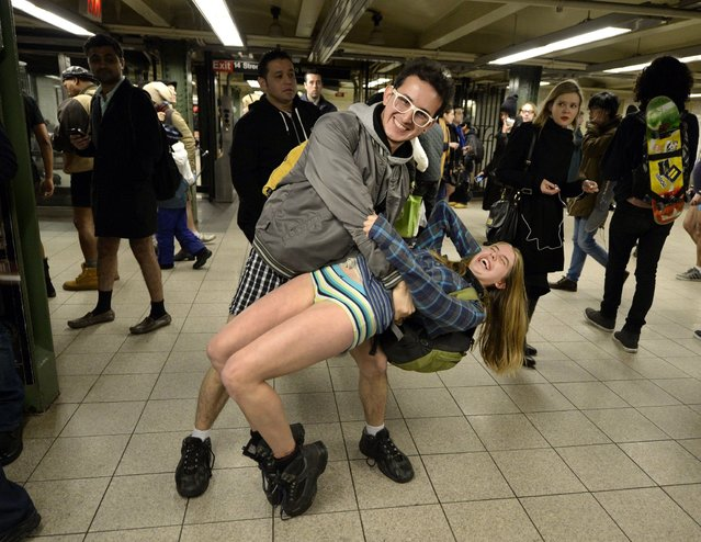 Riders joke as they wait for a train in the New York subway in their underwear while taking part in the 2014 No Pants Subway Ride on January 12, 2014. Started by Improv Everywhere, the goal is for riders to get on the subway train dressed in normal winter clothes without pants and keep a straight face. (Photo by Timothy Clary/AFP Photo)